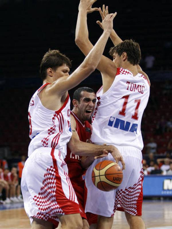 Veisi of Iran drives to the basket between Tomas and Tomic of Croatia during their FIBA Basketball World Championship game in Istanbul