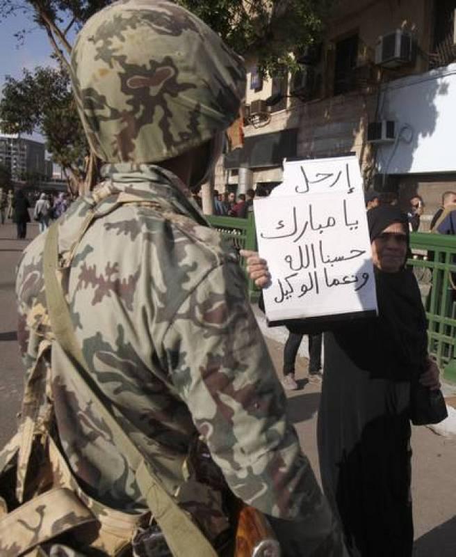 """Una mujer se pasea delante de un soldado con un cartel en el que se puede leer """"Mubarak, vete. Dios nos ayuda""""."""