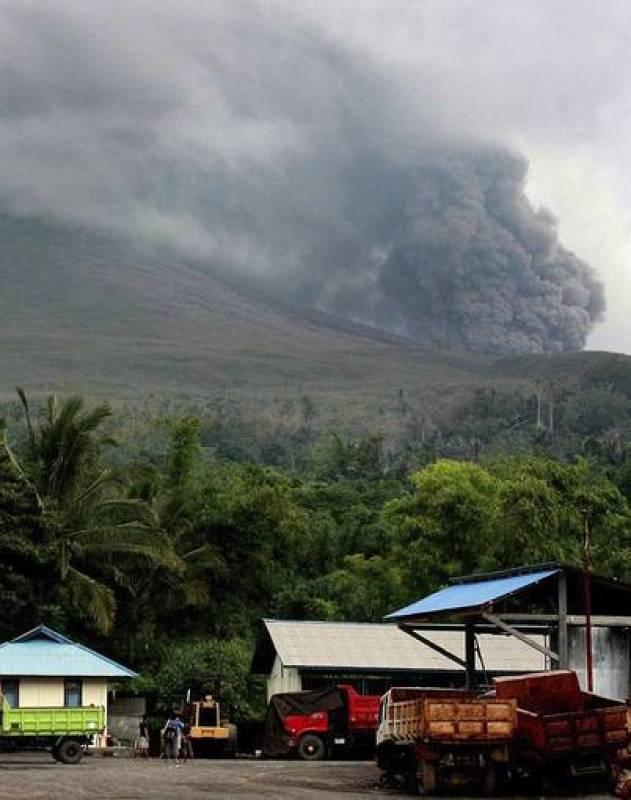 Varios trabajadores indonesios miran como el volcán Lokon arroja gases y cenizas