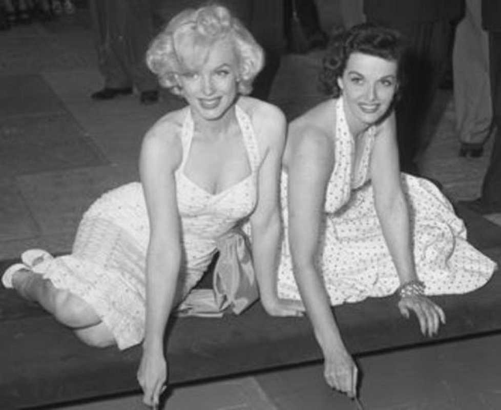 Marilyn Monroe y Jane Russell estampando sus huellas en el cemento en el Teatro Chino de Los Ángeles, California, en 1953.