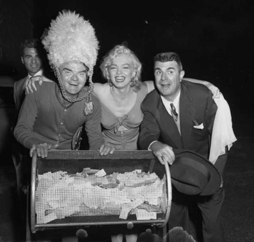 Marilyn Monroe con Spike Jones y Ken Murray posando para la cámara en el octavo partido de fútbol anual para la caridad de Los Angeles Times.