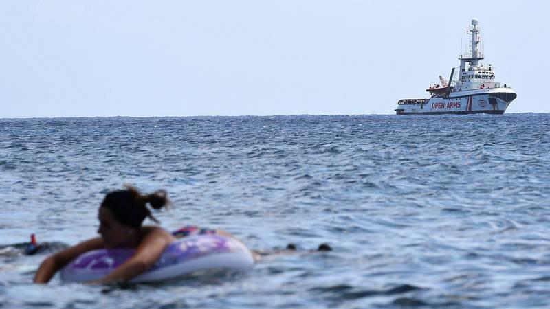 El barco de Open Arms, frente a la costa de Lampedusa, con bañistas en primer término. REUTERS/Guglielmo Mangiapane