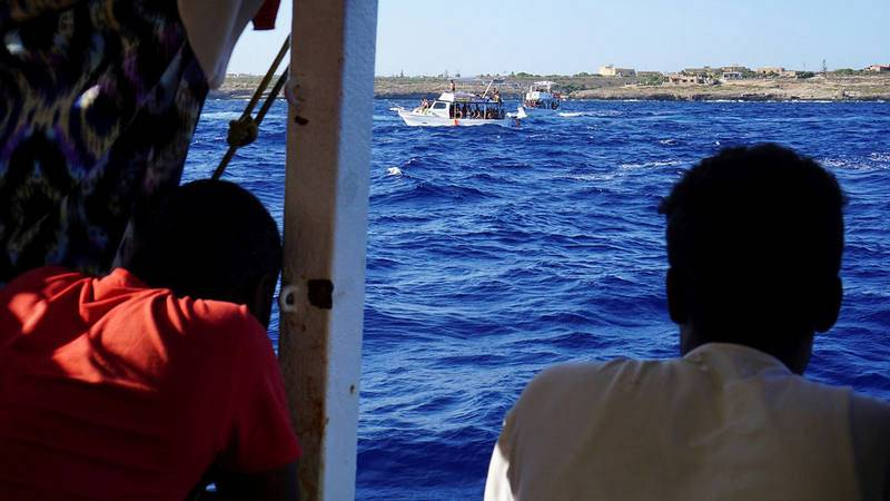 Algunos de los 107 migrantes en el interior del barco de la ONG españolaOpenArms, que sigue bloqueado desde hace 18 días junto a la isla italiana de Lampedusa. EFE/Francisco Gentico
