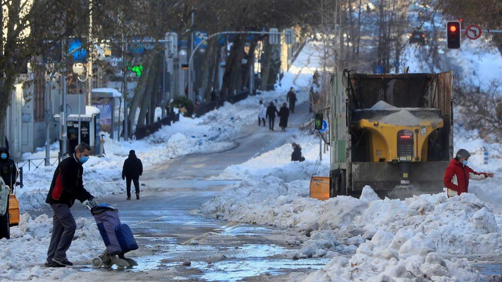 Varias personas transitan una calle de Madrid junto a un quitanieves que trabaja en labores de limpieza, este lunes tras el paso de la borrasca Filomena.