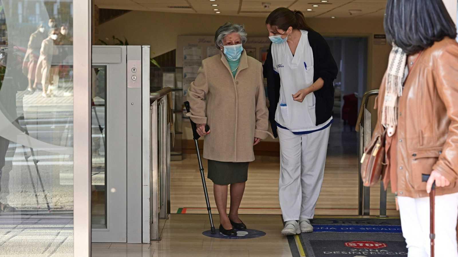 Una mujer recoge a su madre para salir a dar un paseo por el exterior la residencia, tras recibir la vacuna contra la COVID-19.