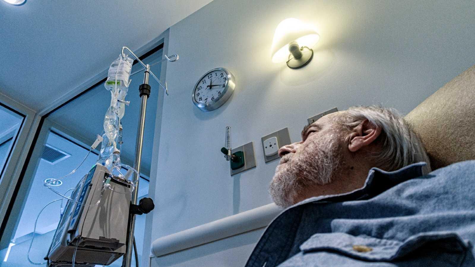 Un paciente de cáncer mira la hora en un reloj mientras recibe su tratamiento.