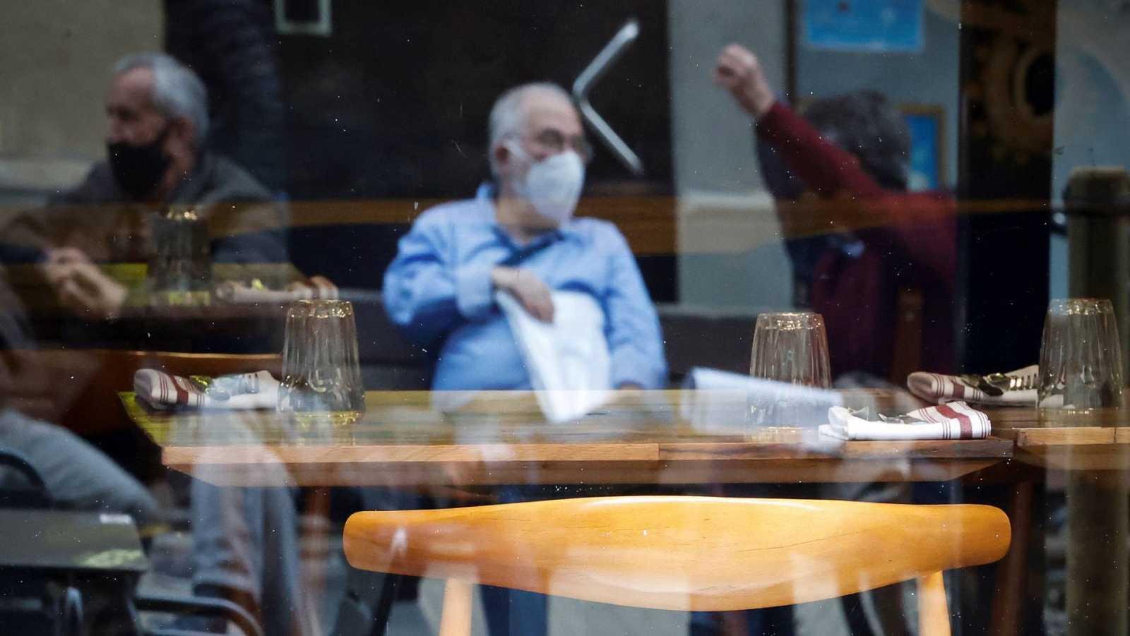 Varios hombres conversan junto a un restaurante vacío en San Sebastián