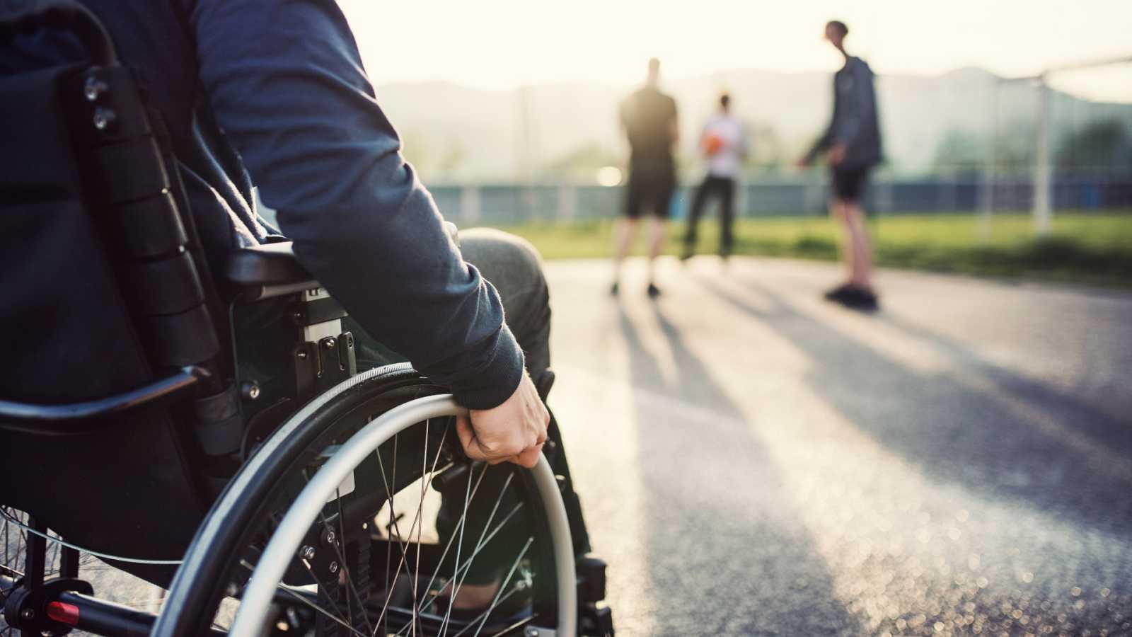 Una persona con discapacidad física se desplaza en silla de ruedas por la calle.
