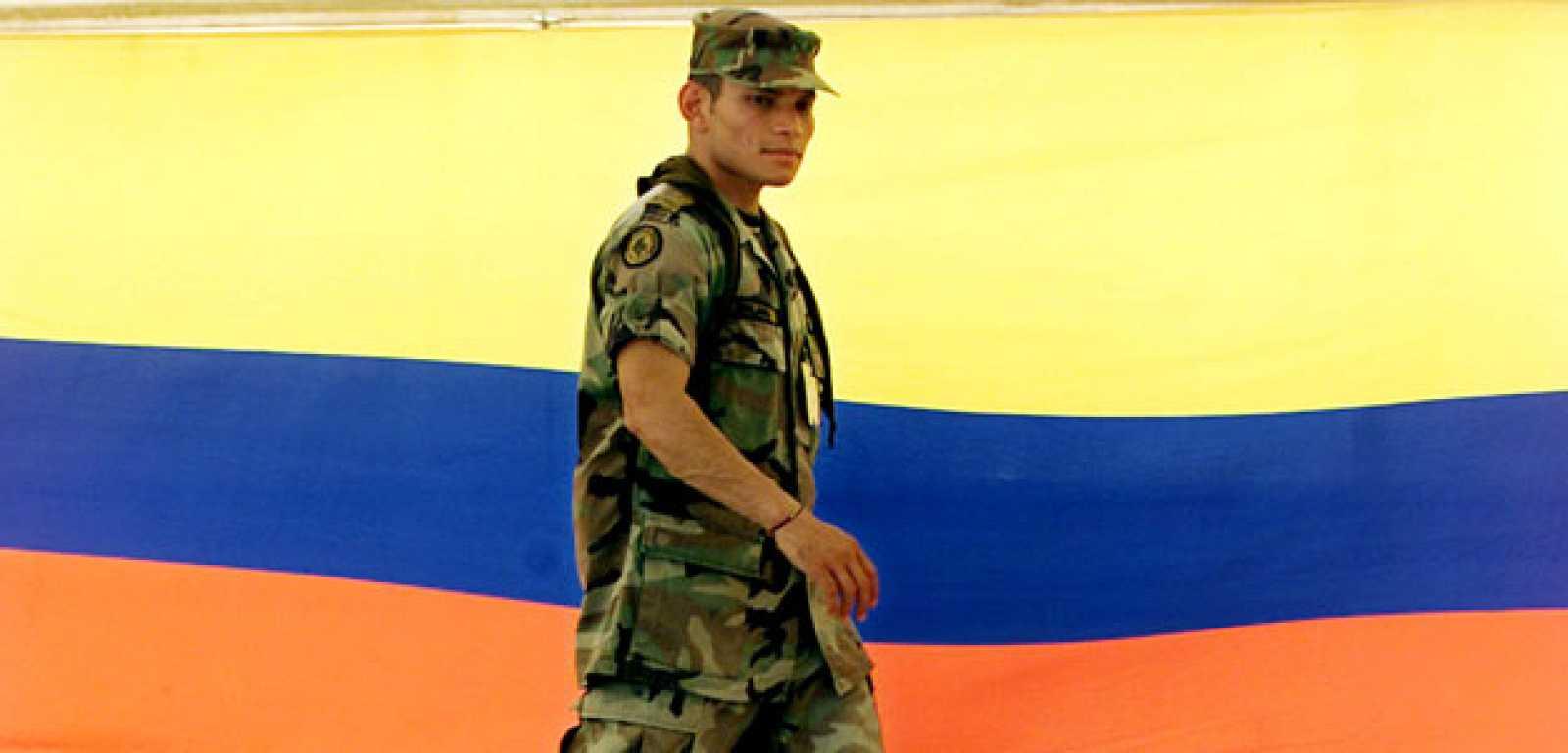Un soldado colombiano pasa por delante de una gran bandera del país.