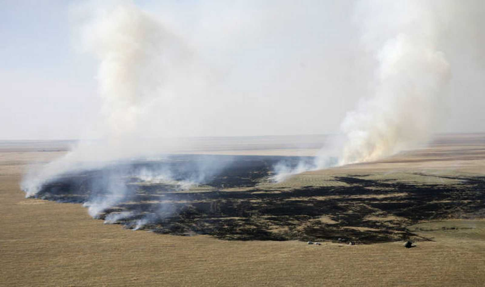 Smoke rises at the area where the Soyuz capsule landed in northern Kazakhstan