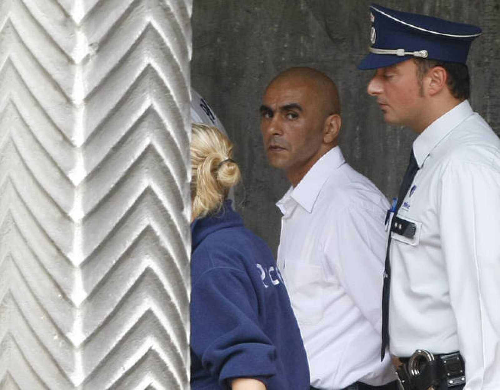 Abdallah Ait Oud, escoltado por un policía, en el primer día de su juicio en Lieja acusado de violar y asesinar a dos niñas.