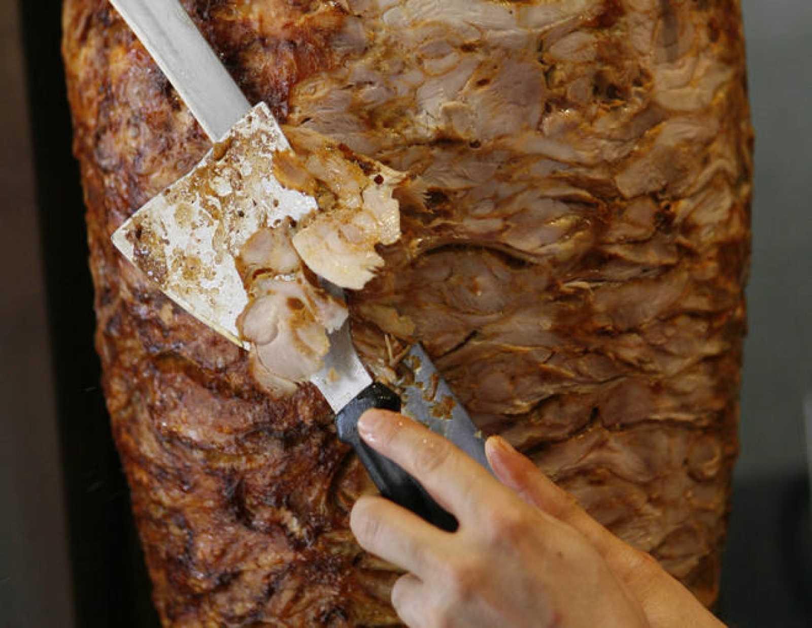 Un trabajador corta una tira de kebab en un restaurante de Dortmund, Alemania.