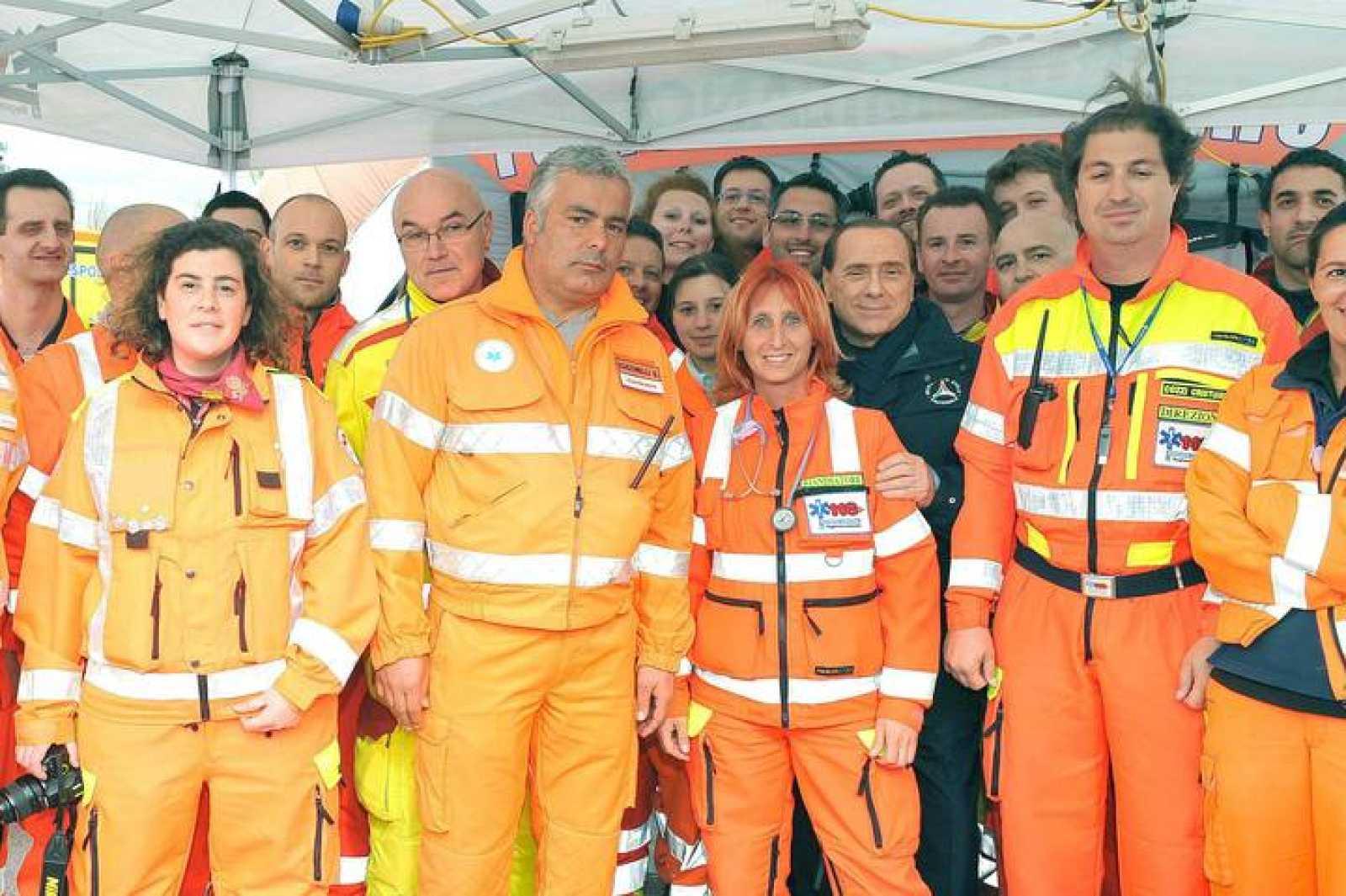 Berlusconi, tras la médico a la que ha cubierto de halagos, posando con el personal de Protección Civil.