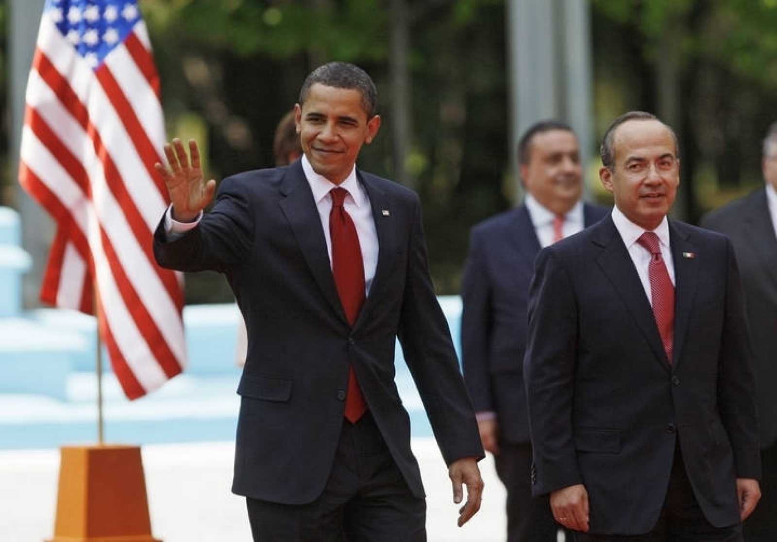 U.S. President Obama waves as he walks with Mexico's President Calderon in Mexico City