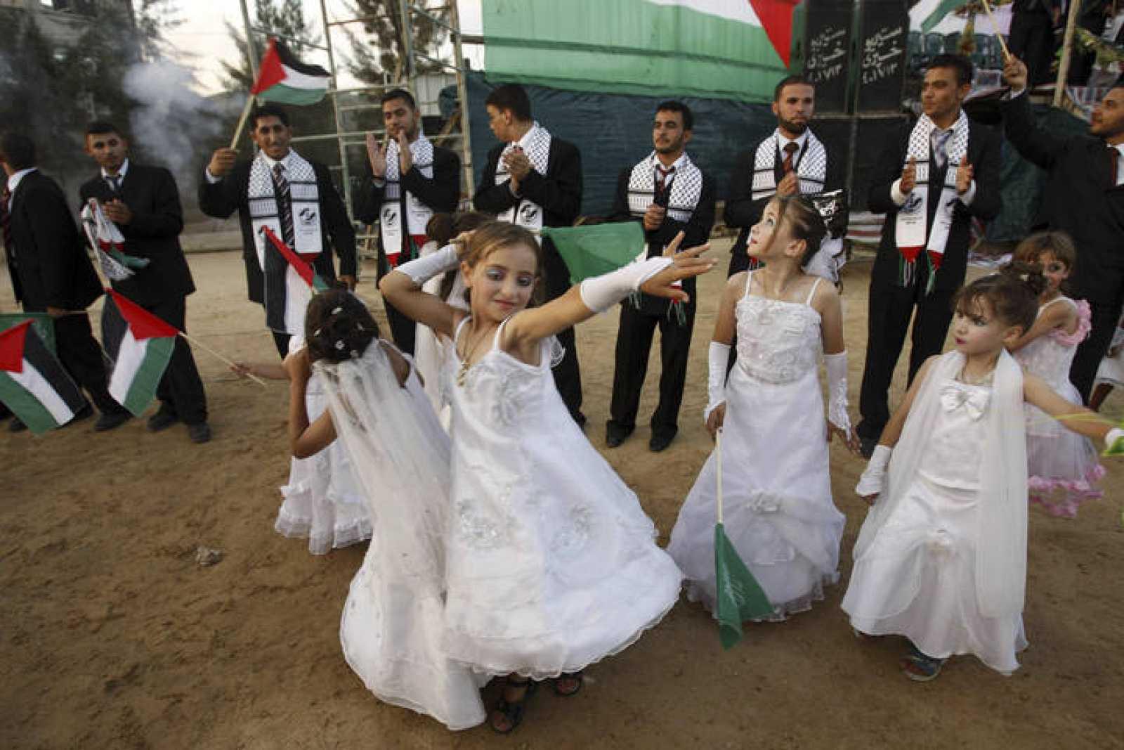 Niñas bailan ante los novios en una boda masiva en Gaza.
