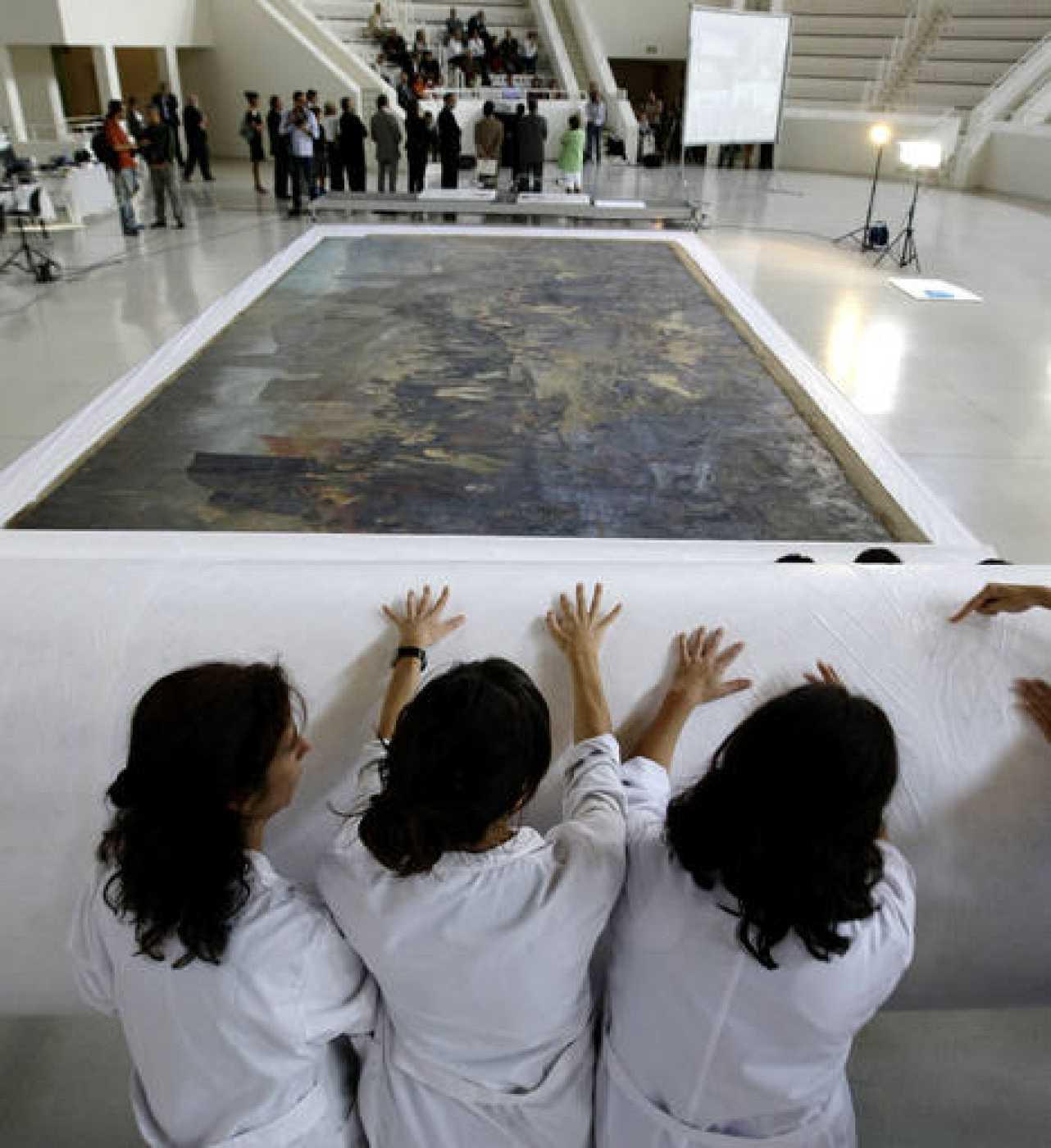 Tres restauradoras cubren con un papel protector una pintura