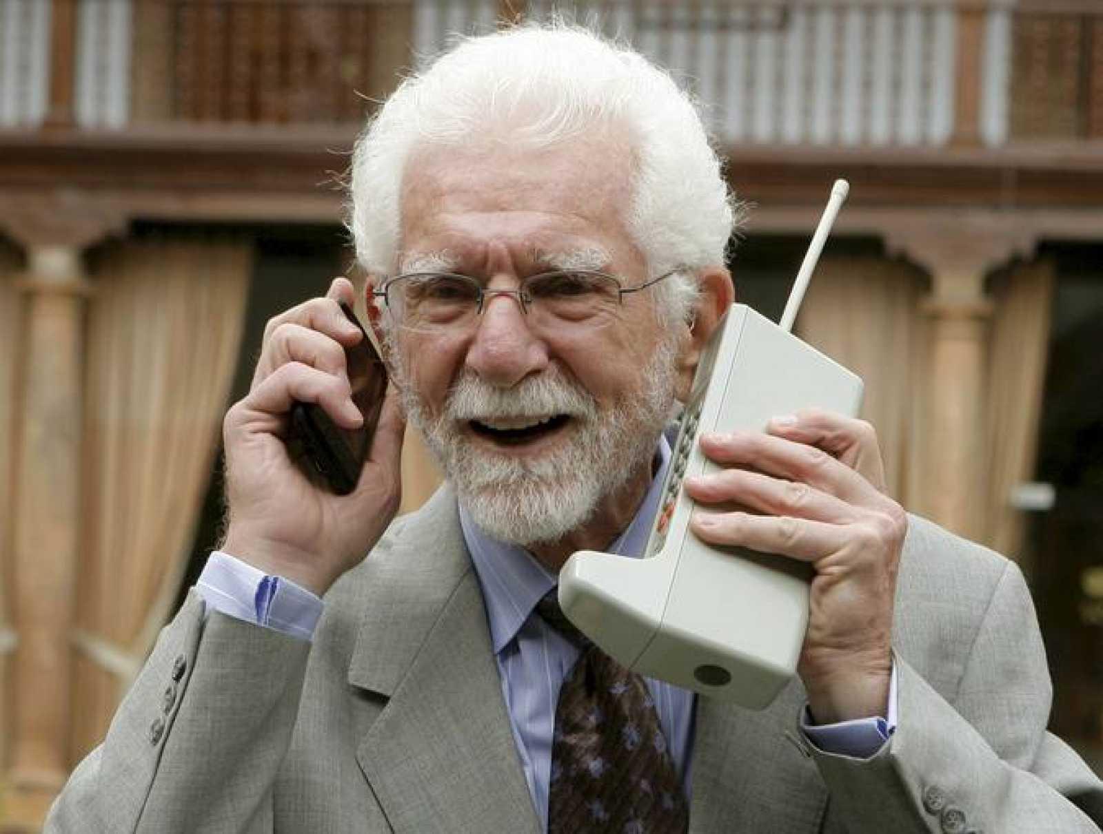 El ingeniero norteamericano Martin Cooper posa con dos modelos de teléfono móvil en Oviedo donde recogerá el premio Príncipe de Asturias.
