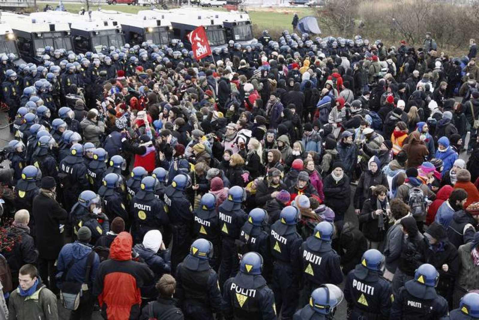 Policías vigilan a los manifestantes de la cumbre de la ONU sobre Cambio Climático en Copenhague.