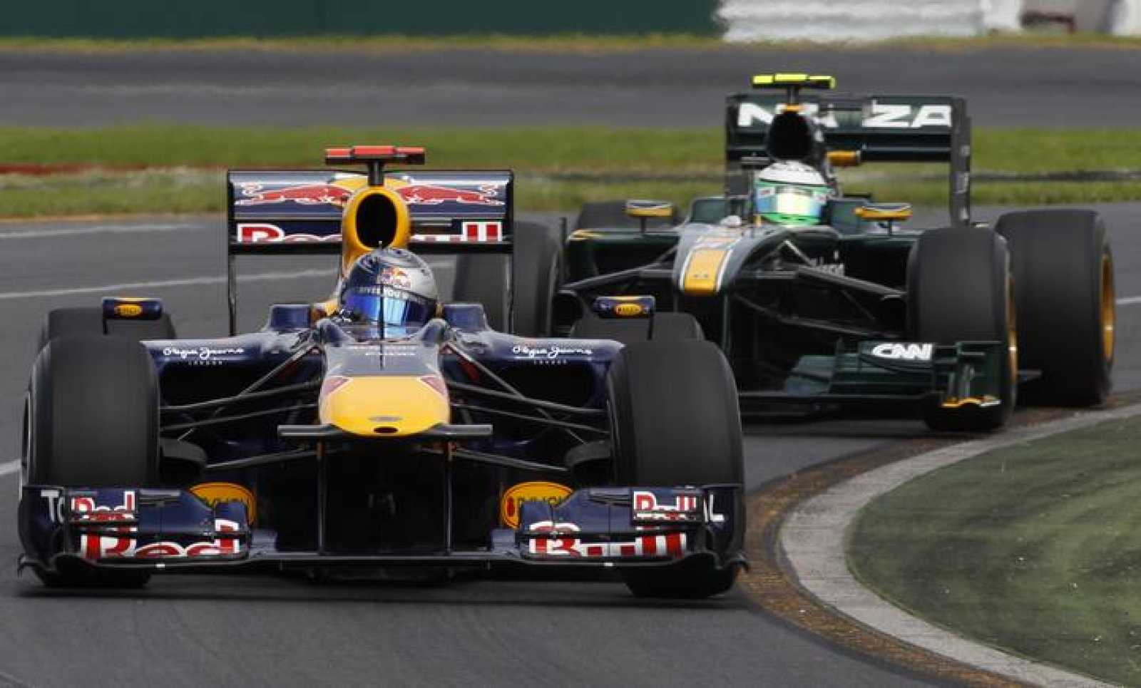Red Bull Formula One driver Sebastian Vettel of Germany drives ahead of Lotus F1 driver Heikki Kovalainen of Finland during the first practice session of the Australian F1 Grand Prix in Melbourne