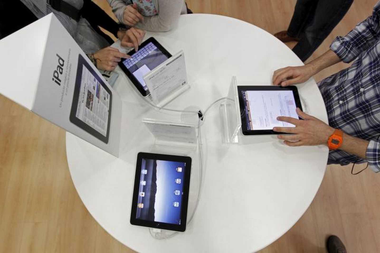 Varios jóvenes prueban el iPad, el nuevo dispositivo de Apple que ya está  en las tiendas españolas, dos meses después de su lanzamiento en Estados Unidos.