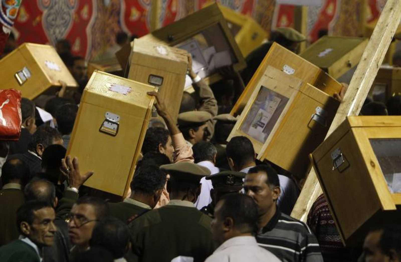 Oficiales de policía portan las urnas con los votos de las elecciones en Egipto