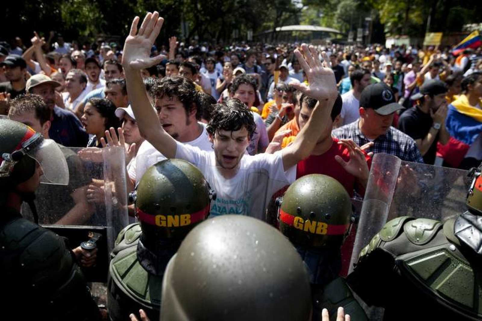 Venezuelan riot guards clash with students during a protest against Venezuela's President Hugo Chavez in Caracas