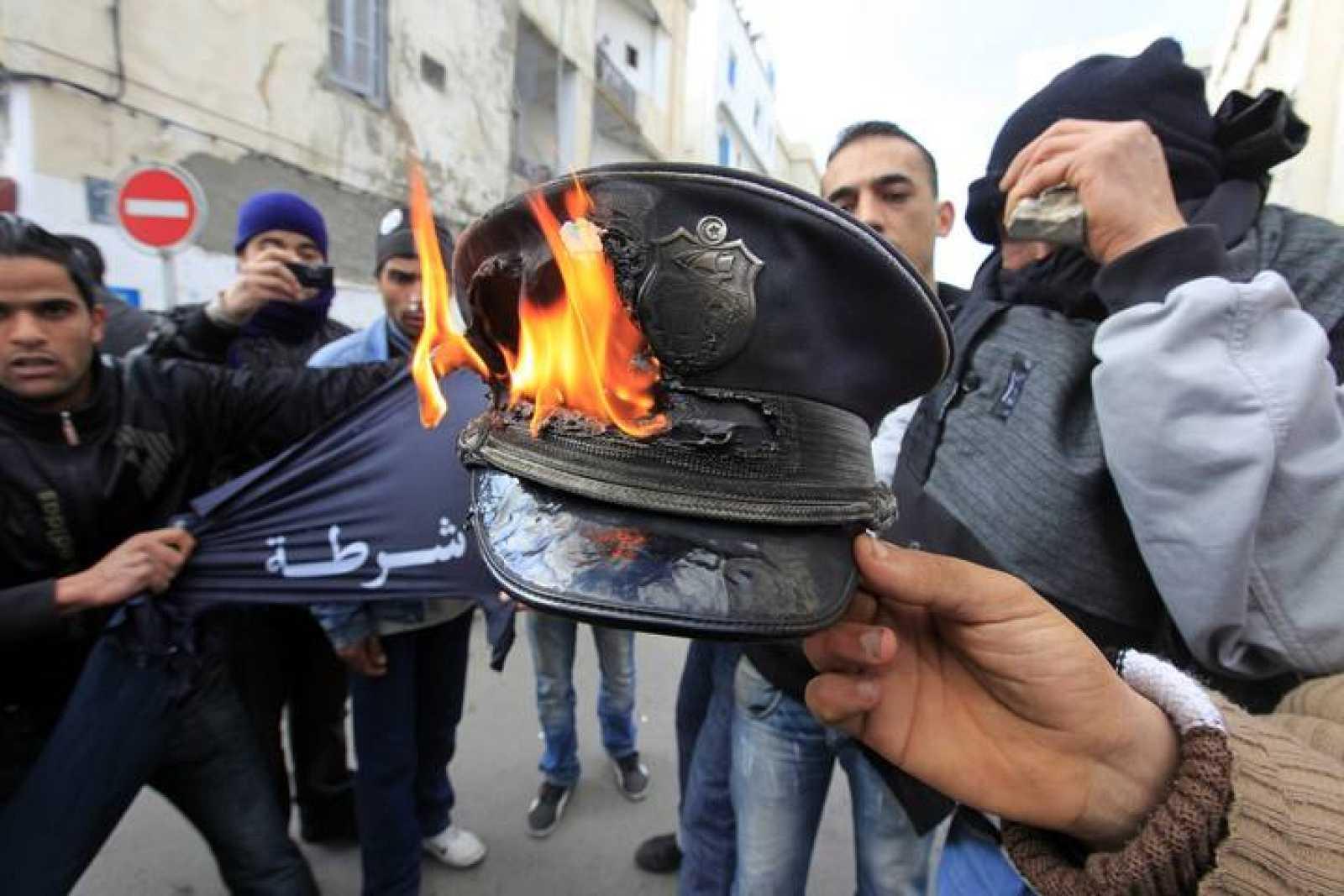 Manifestantes queman un gorro de Policía durante los choques en Túnez.