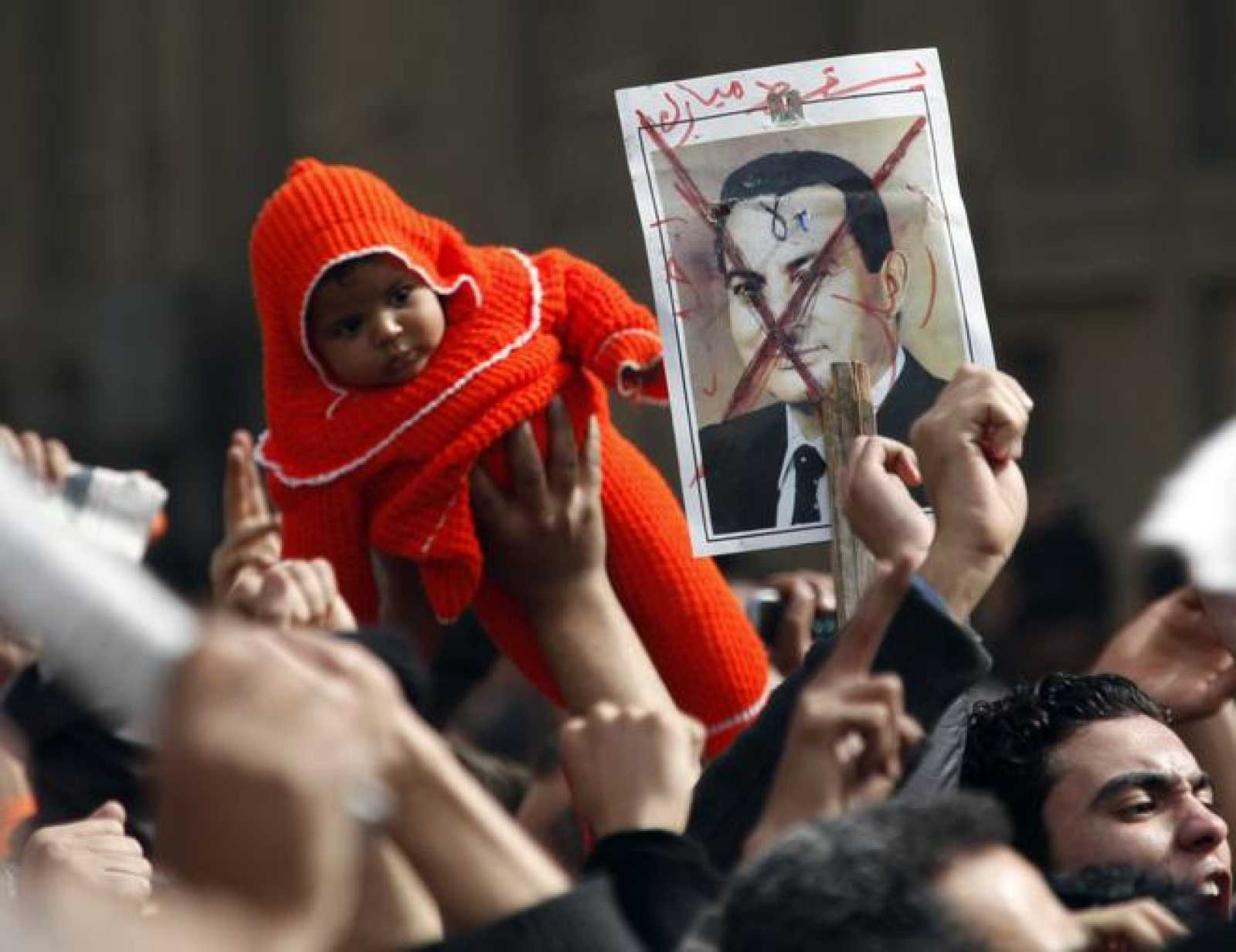 A protester holds up a child in front of a picture of Egypt's President Hosni Mubarak during a protest in Cairo