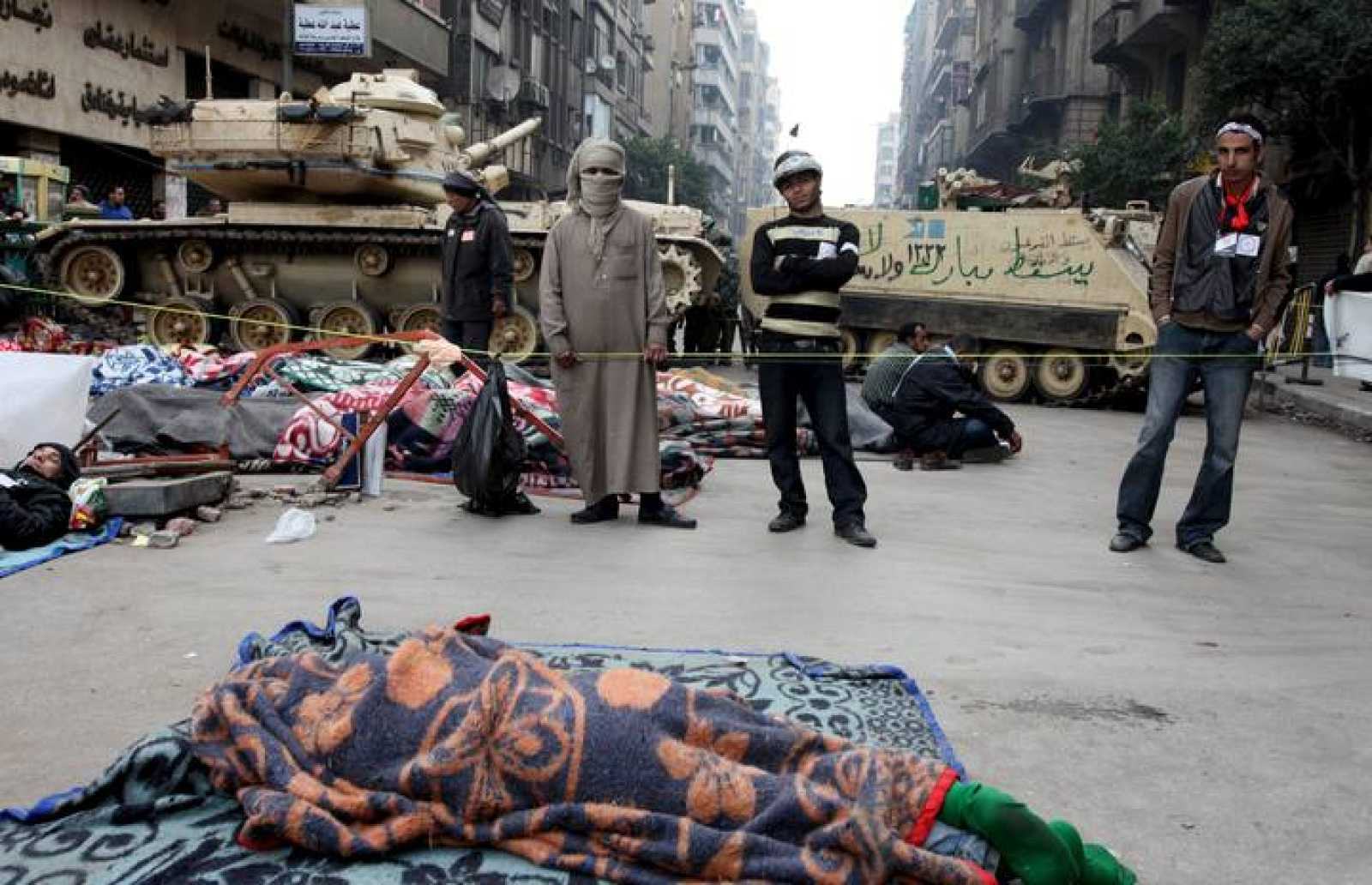 Manifestantes opositores al Gobierno permanecen en un puesto de control montado por civiles cerca de un tanque del ejército mientras otras personas duermen en una calle que conduce a la plaza Tahrir en El Cairo