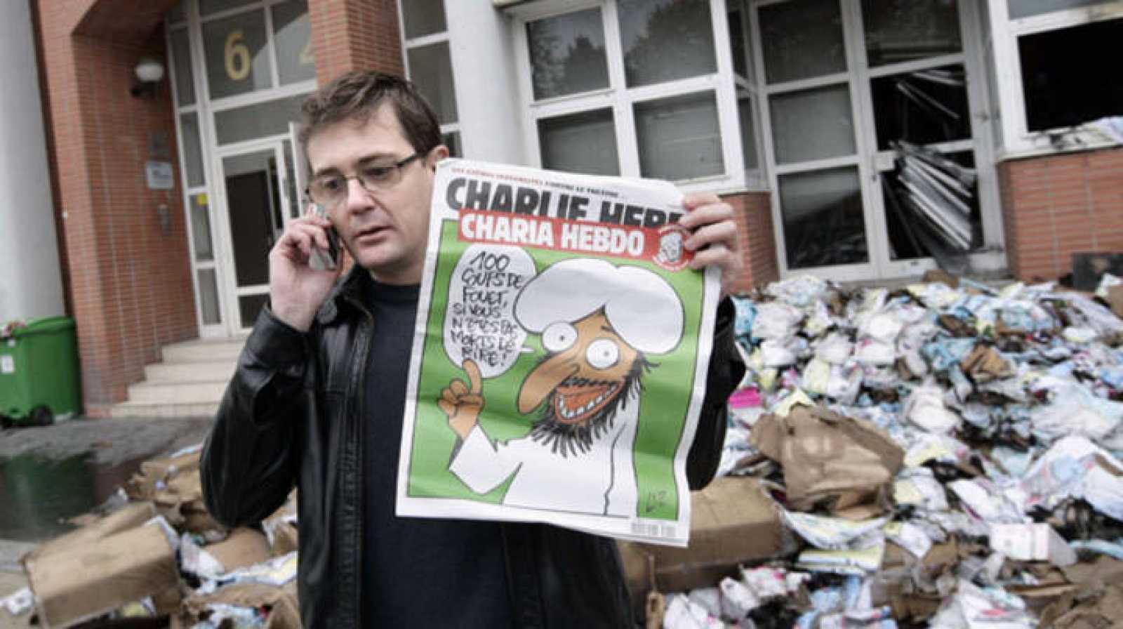 El editor de Charlie Hebdo, conocido como Charb, muestra un ejemplar del último número frente a la sede del diario que ha sido atacada