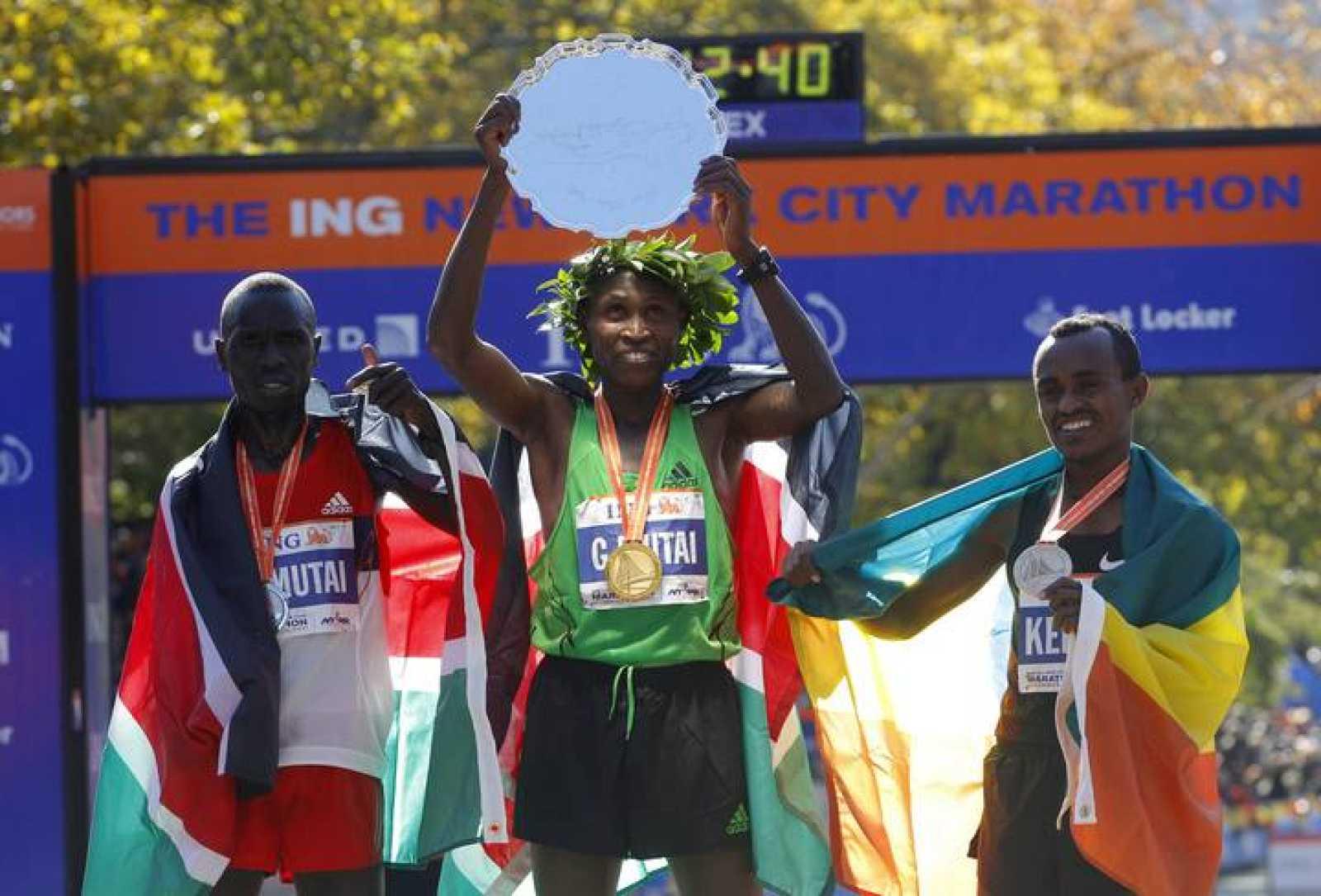 Mutai of Kenya raises the winner's trophy after winning the 2011 New York City Marathon in New York