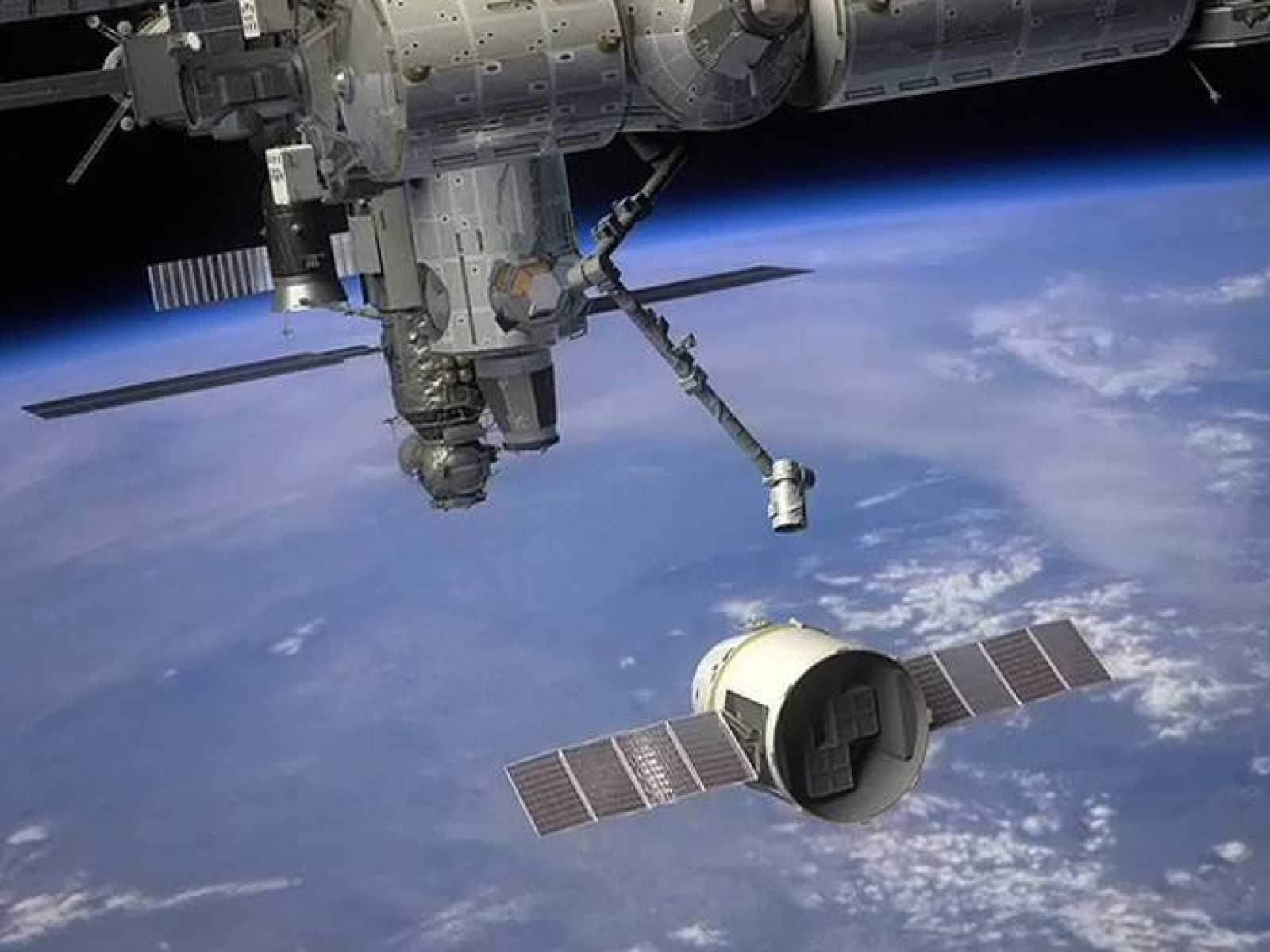 Impresión artística del brazo robot de la Estación Espacial Internacional capturando la Dragon