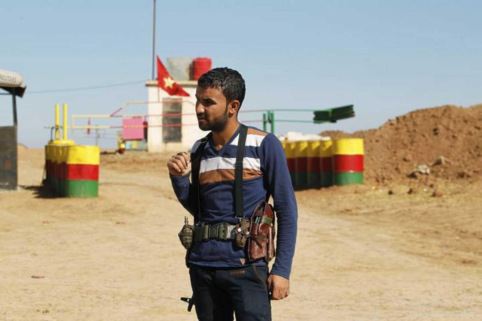 Un miembro de la milicia del Partido de la Unión Democrática (PYD) hace guardia junto a un puesto de control en la frontera sirio-iraquí