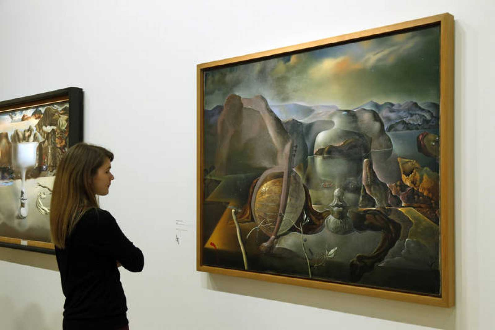"A visitor looks at a painting by Salvador Dali during a press visit of the exhibition ""Dali"" at the Centre Pompidou modern art museum in Paris"