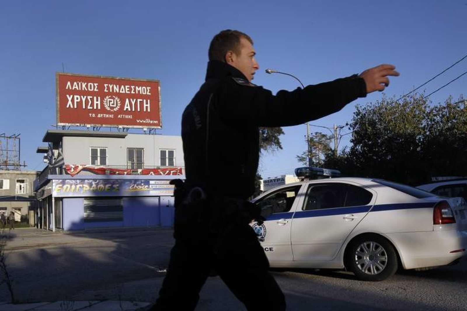 Un policía griego dirige el tráfico frente a la sede del partido neonazi Amanecer Dorado en Aspropyrgos, atacada con un artefacto explosivo