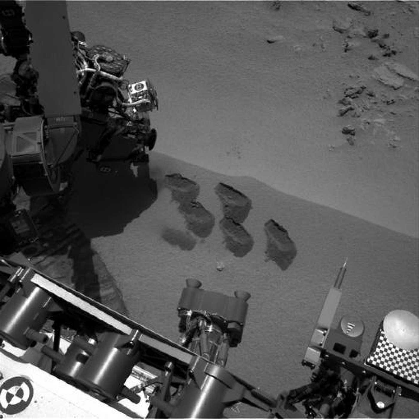 Imagen de la NASA donde se ven cinco marcas en la superficie marciana, tomada por la pala del brazo robótico del Curiosity.