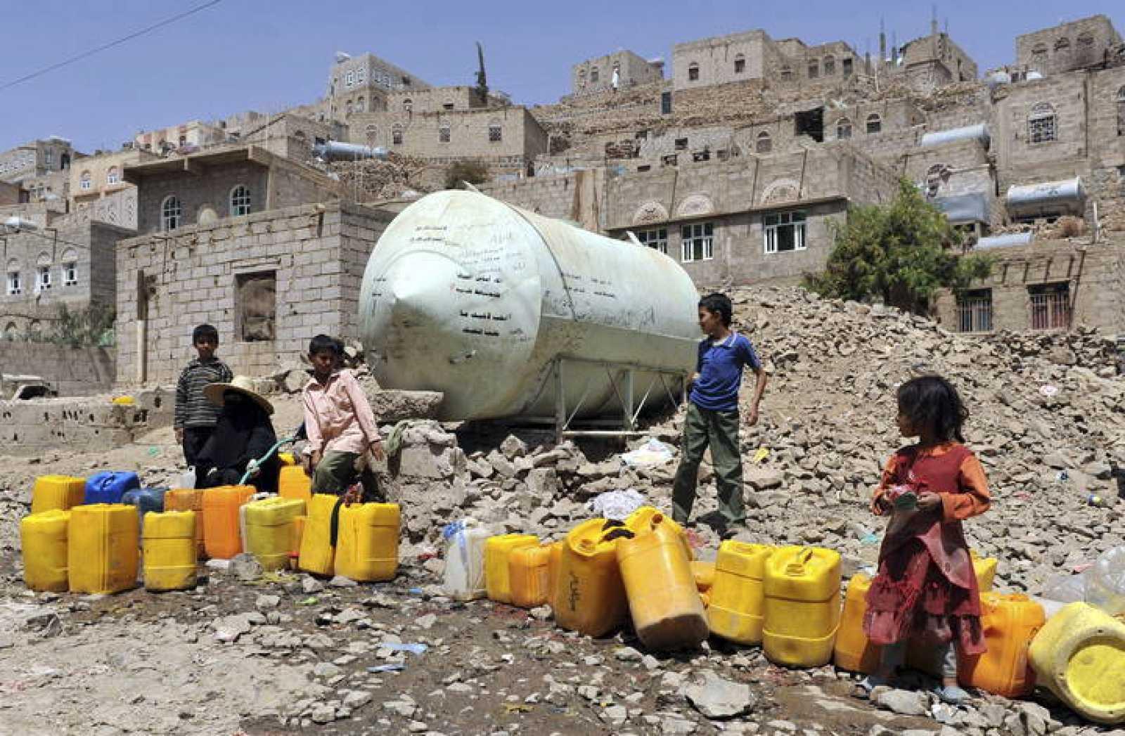 Una mujer y unos niños llenan bidones de agua de una tubería pública en una barriada pobre de Saná (Yemen).