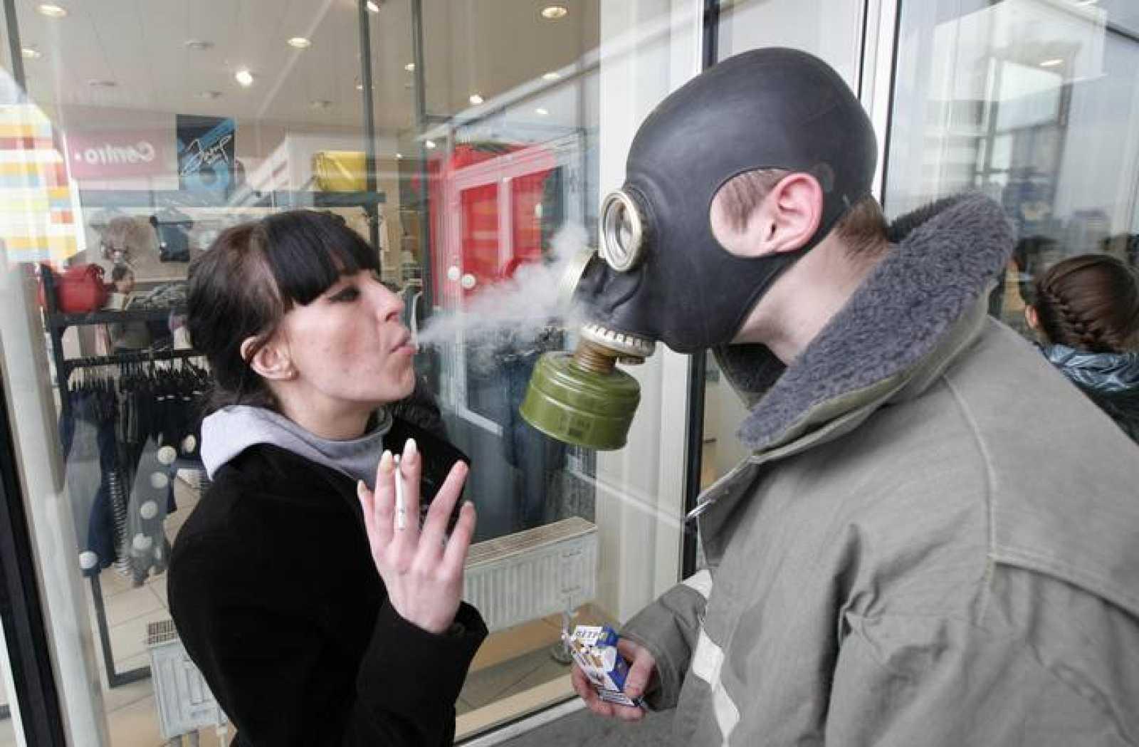 Una mujer lanza humo sobre un activista que lleva una máscara antigás e nun protesta anti tabaco en Rusia.