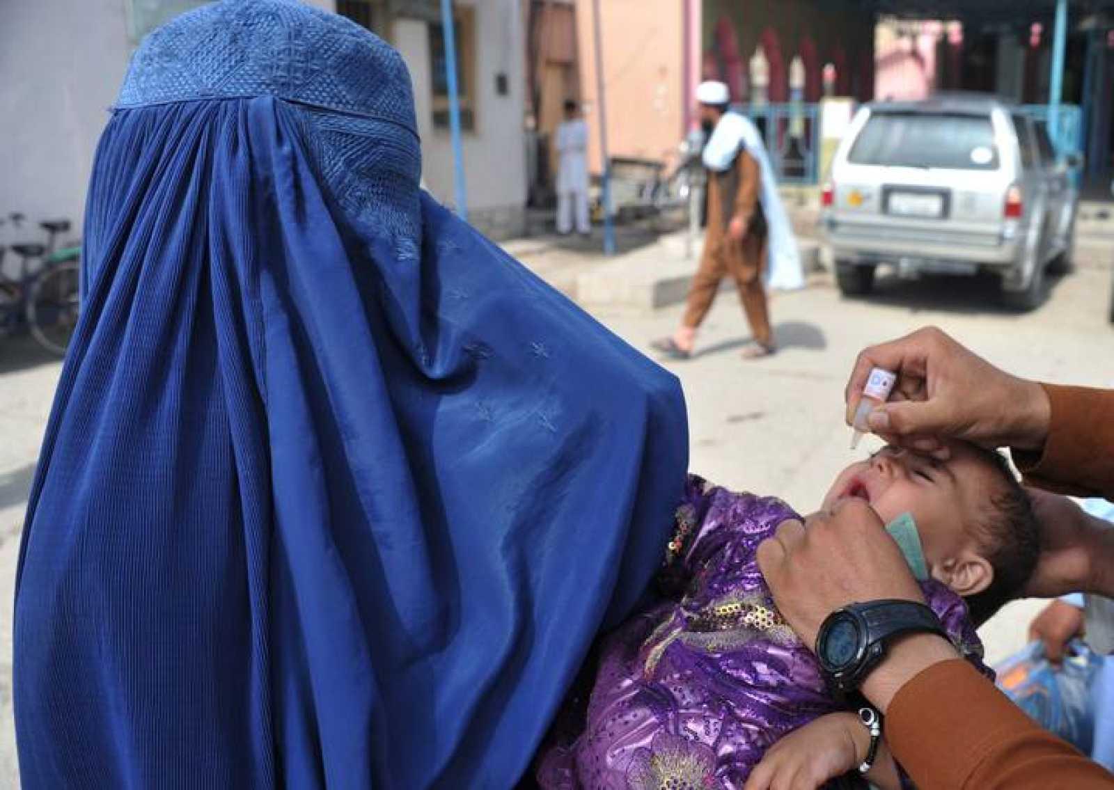 Un empleado sanitario afgano administra la vacuna contra la polio a un niño en Jalalabad