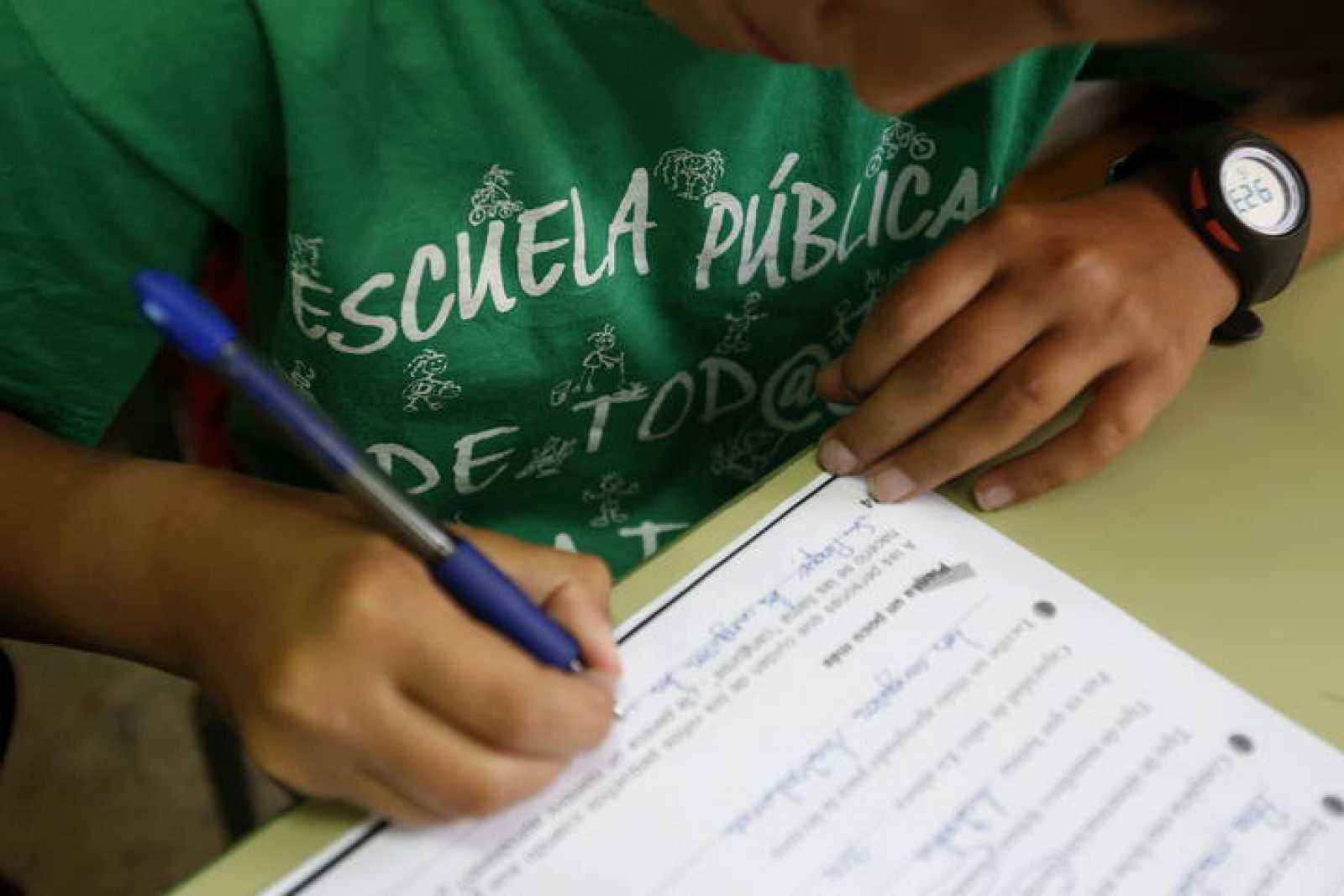 Un alumno del Colegio Joaquín Costa de Madrid rellena una ficha con la camiseta a favor de la escuela pública