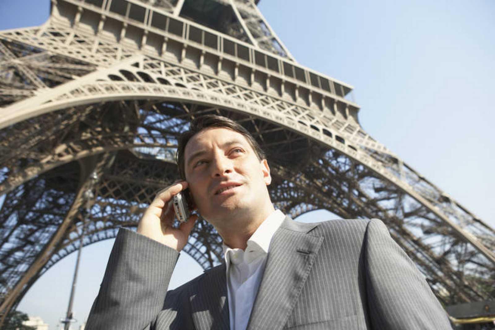 Un hombre de negocios hablando por móvil junto a la Torre Eiffel, en París.