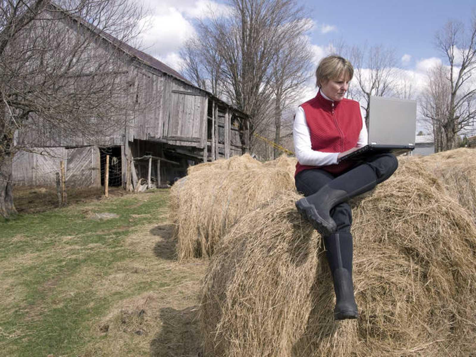 Mujer trabajando con un portátil en una granja.