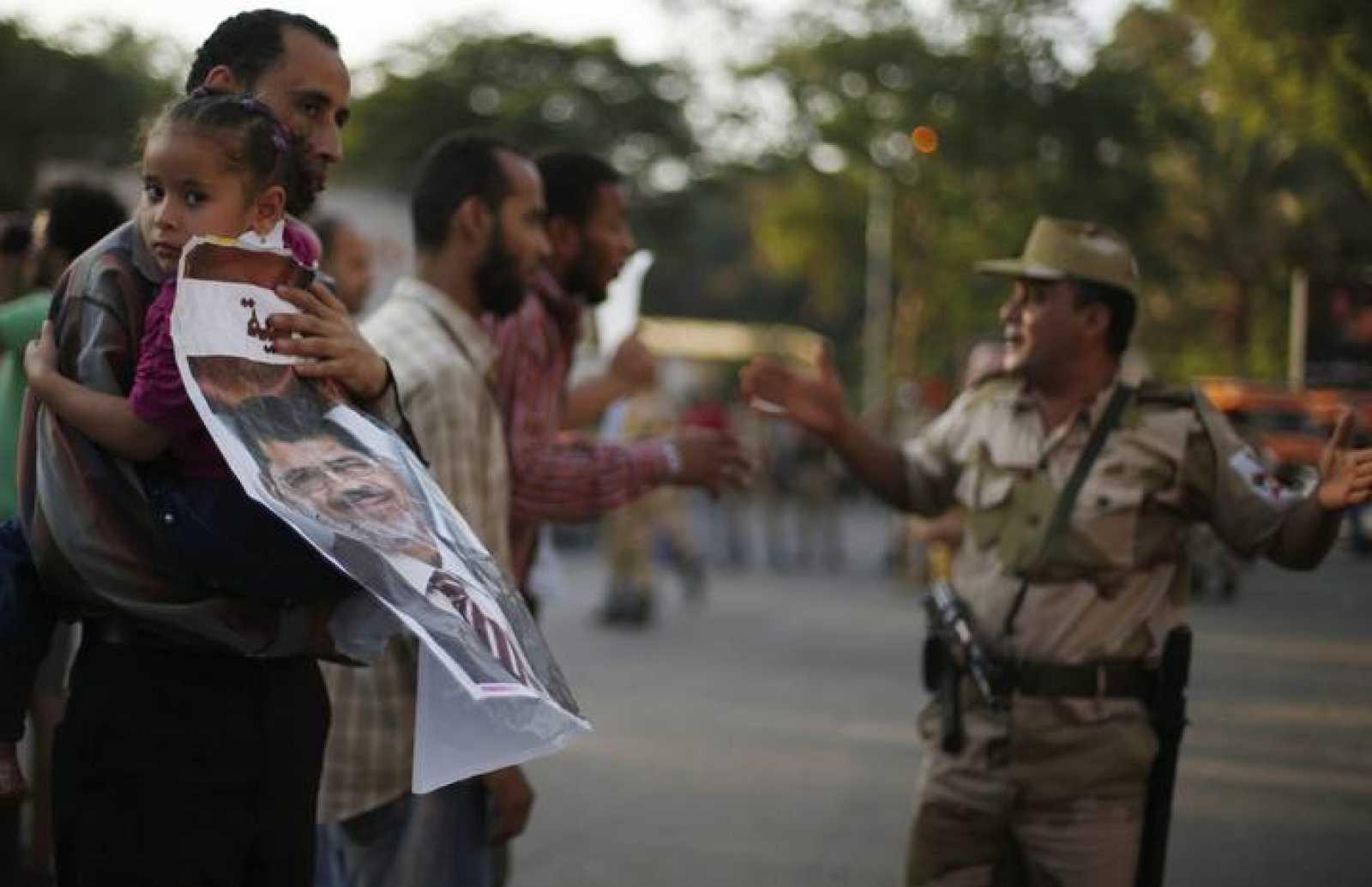 Un manifestante que apoyó el golpe contra Morsi conversa con un miembro del Ejército.