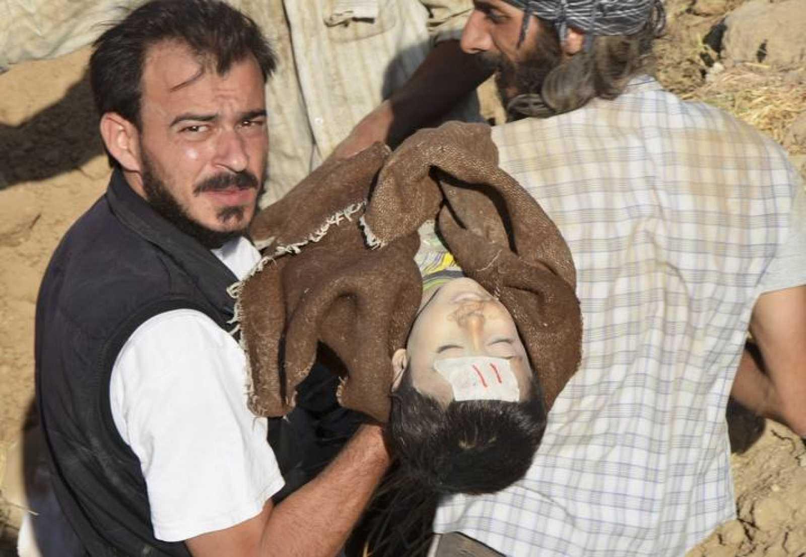 Un hombre traslada el cuerpo de una de las víctimas del supuesto ataque químico para su funeral en Hamoria, Siria.
