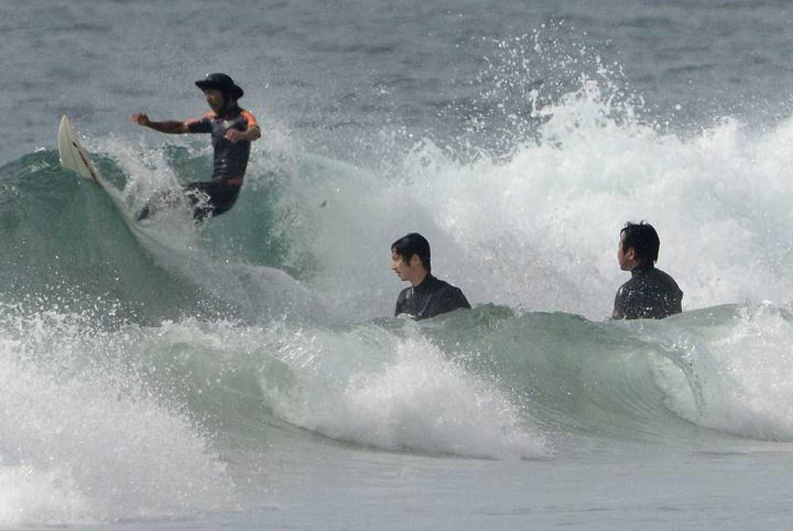 Surferos en una playa a 50 km de la central nuclear de Fukushima.