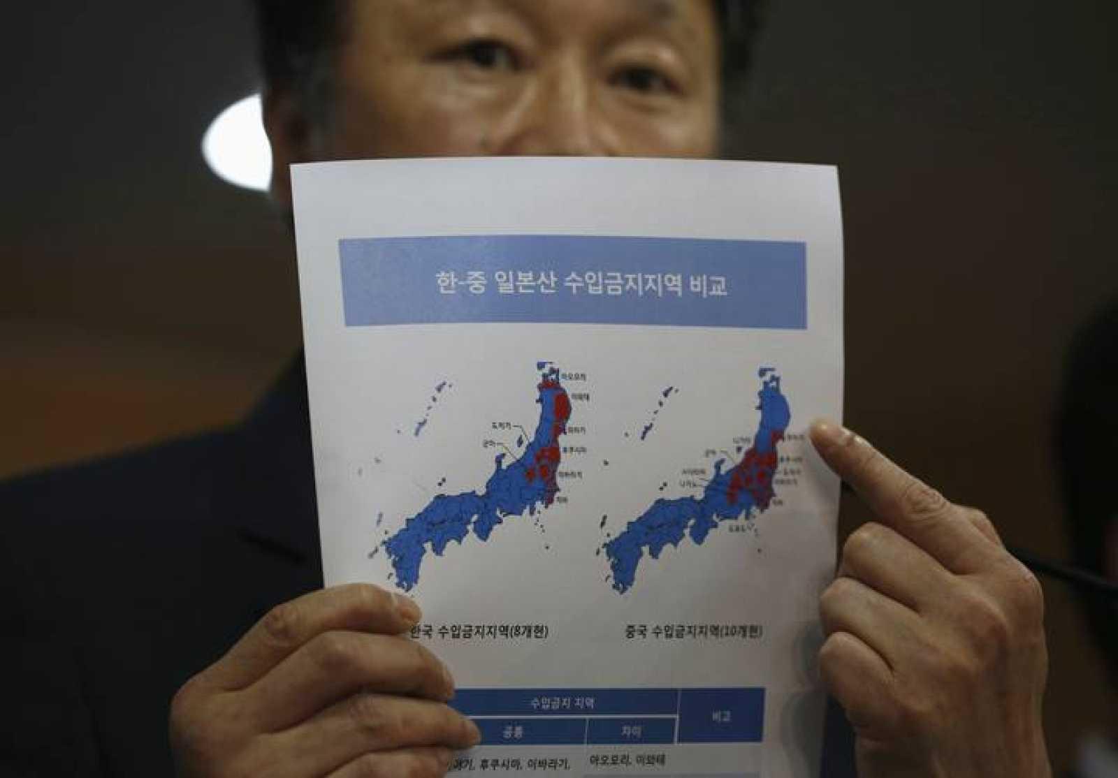 El viceministro surcoreano de Asuntos Marítimos y Pesca, Son Jae-hak, muestra en un documento las prefecturas japonesas de las zonas prohibiciones de importación (en rojo) impuestas por Corea del Sur y China, respectivamente.