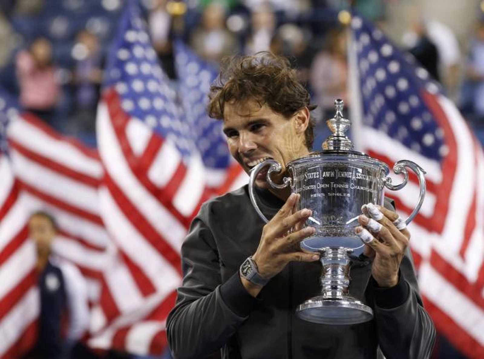 Rafael Nadal celebra su título en el US Open 2013 con su tradicional gesto de morder el trofeo