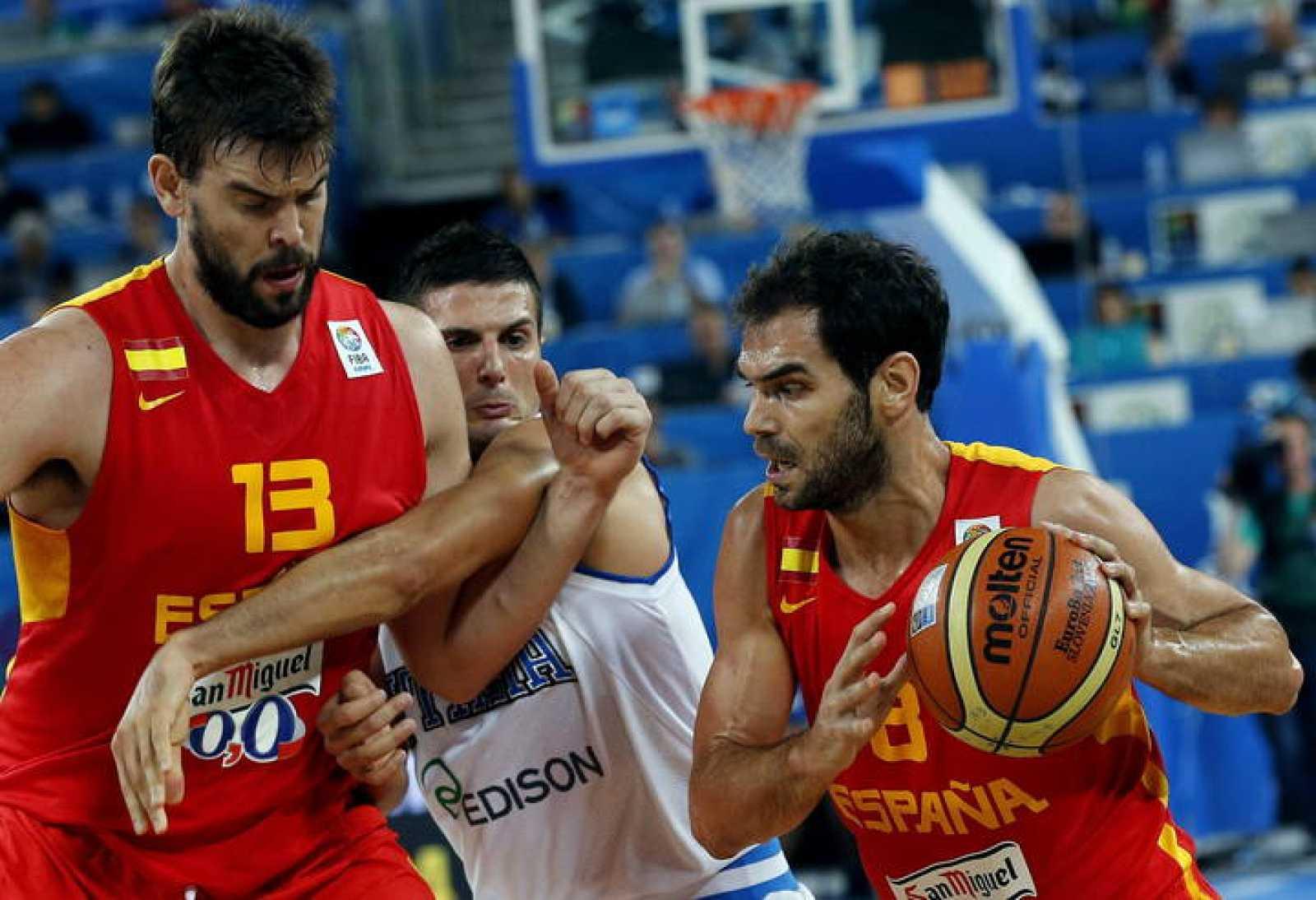 El base de la selección española José Manuel Calderón (d) avanza con el balón mientras el pívot español Marc Gasol bloquea al base italiano Andrea Cinciarini (c)