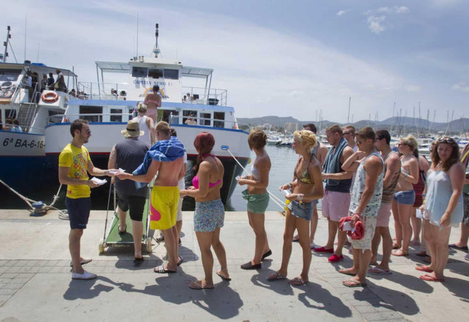 Imagen un joven recogiendo las entradas de los turistas que quieren acceder a un barco recreativo