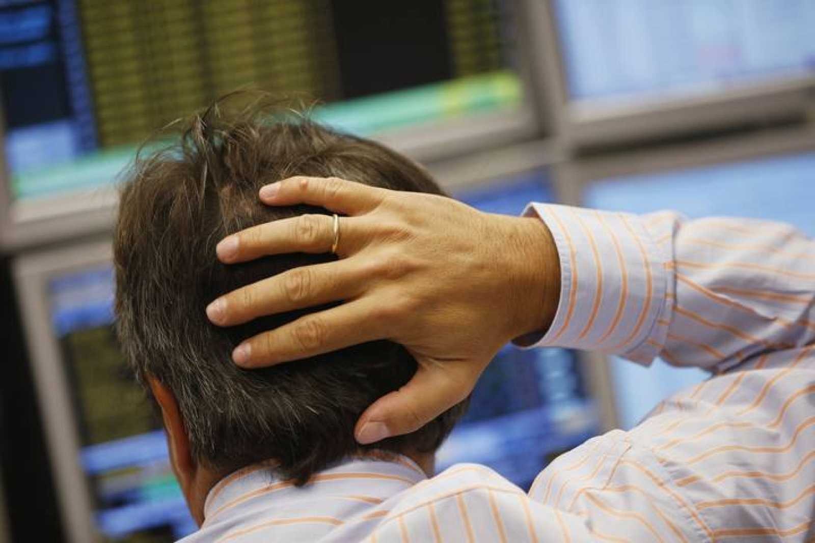 Un empleado de banca mira preocupado la pantalla de un ordenador